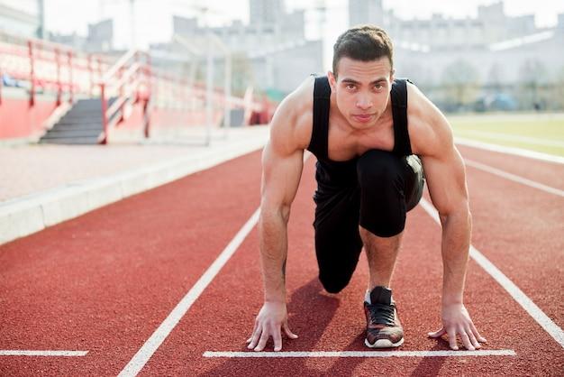 Retrato de um homem que toma a posição para correr na pista de atletismo