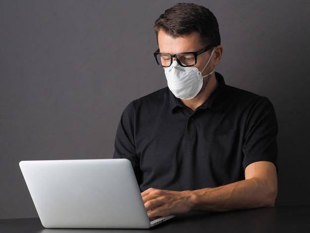 Retrato de um homem que trabalha no escritório no laptop com máscara protetora no rosto. consciência da doença de coronavírus (covid19). as pessoas se protegem do covid-19 ou 2019 ncov.