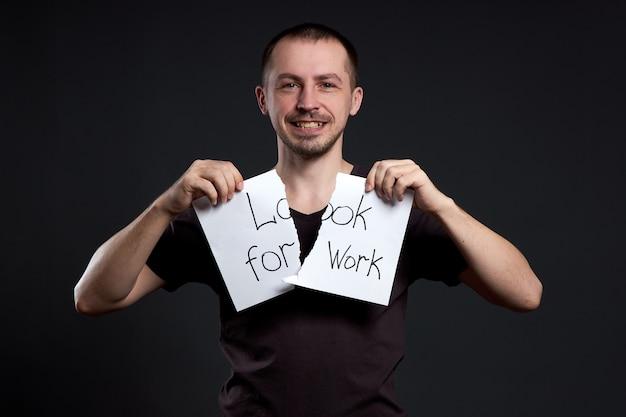 Retrato de um homem rasgando uma inscrição no papel à procura de emprego
