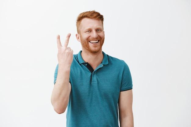 Retrato de um homem ruivo feliz e alegre, de aparência amigável, com barba fazendo dois sinais e sorrindo amplamente enquanto fica de pé sobre uma parede cinza