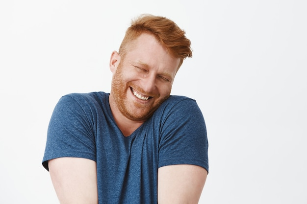 Retrato de um homem ruivo fofo, satisfeito e feliz, feliz e engraçado, de camiseta azul, encolhendo os ombros e apoiando o rosto no ombro enquanto sorri amplamente, corando de alegria e felicidade