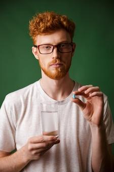 Retrato de um homem ruivo jovem sério de óculos