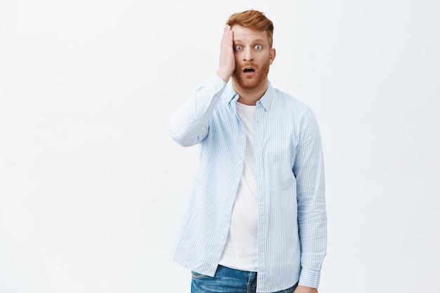 Retrato de um homem ruivo maduro e arrasado e atordoado em uma camisa, segurando a palma da mão no rosto e deixando cair o queixo de tremer