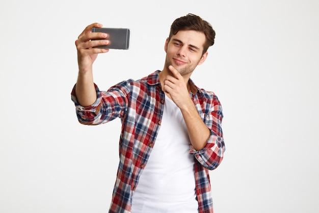 Retrato de um homem satisfeito tomando uma selfie em pé