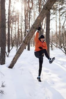 Retrato de um homem se alongando no parque em um lindo dia de neve de inverno, preparando-se para correr