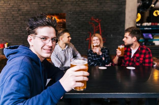 Retrato, de, um, homem, segurando, a, vidro cerveja, sentar-se, com, amigos