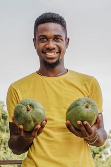 Retrato de um homem segurando frutas orgânicas