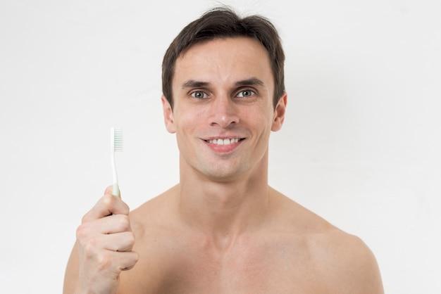 Retrato, de, um, homem, segurando, um, escova de dentes
