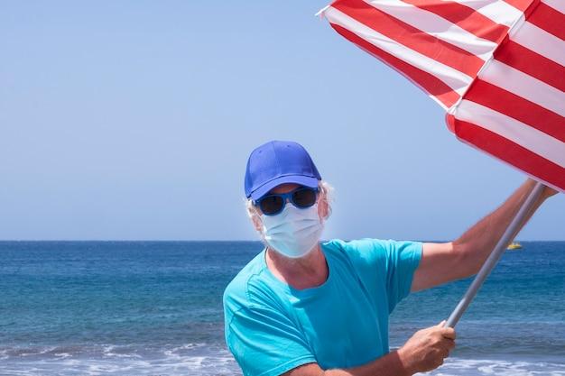 Retrato de um homem sênior com cabelo branco e máscara facial devido a coronavírus em pé na praia pegando guarda-chuva voando por causa do vento - horizonte azul sobre a água nas férias de verão