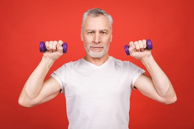 Retrato de um homem sênior exercitar com halteres.