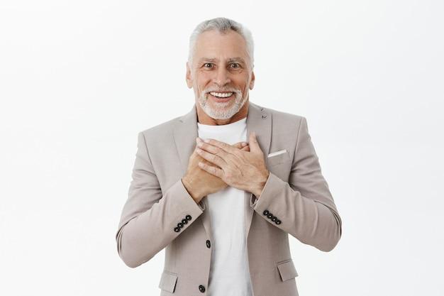 Retrato de um homem sênior feliz e animado, parecendo lisonjeado e surpreso, segurando as mãos no peito