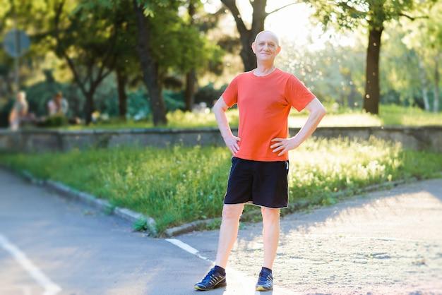 Retrato de um homem sênior feliz e ativo posando depois de se exercitar ao ar livre