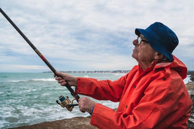 Retrato de um homem sênior pescando no mar, curtindo a vida. pesca e conceito de esporte.