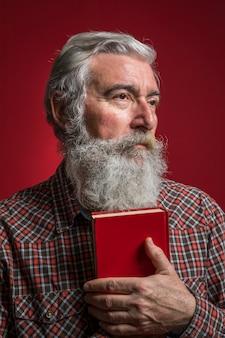 Retrato, de, um, homem sênior, segurando, livro vermelho, em, mão, contra, experiência colorida