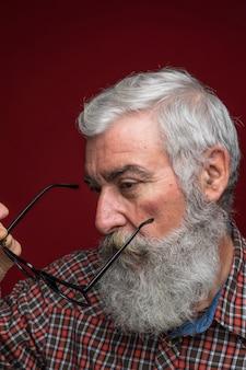 Retrato, de, um, homem sênior, segurando, óculos, em, mão, ficar, contra, colorido, fundo
