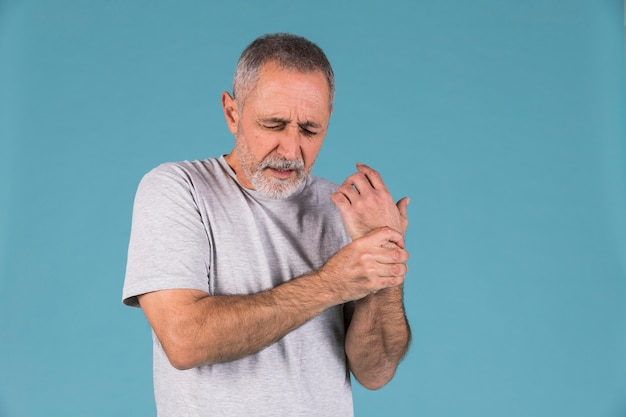 Retrato, de, um, homem sênior, segurando, seu, ferido, pulso