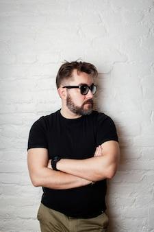 Retrato de um homem sério barbudo em óculos de sol.