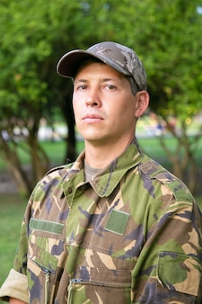 Retrato de um homem sério com uniforme de camuflagem militar em pé no parque,