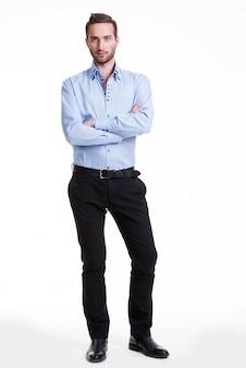 Retrato de um homem sério de camisa azul e calça preta com os braços cruzados - isolado no branco