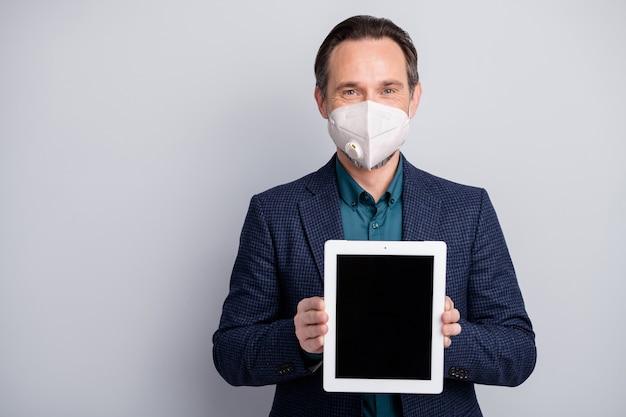 Retrato de um homem sério de meia-idade usando máscara de segurança n95 mostrando display tablet mers cov ncov-2 informações sobre serviços de gripe ajuda a ficar em casa isolado sobre fundo cinza claro