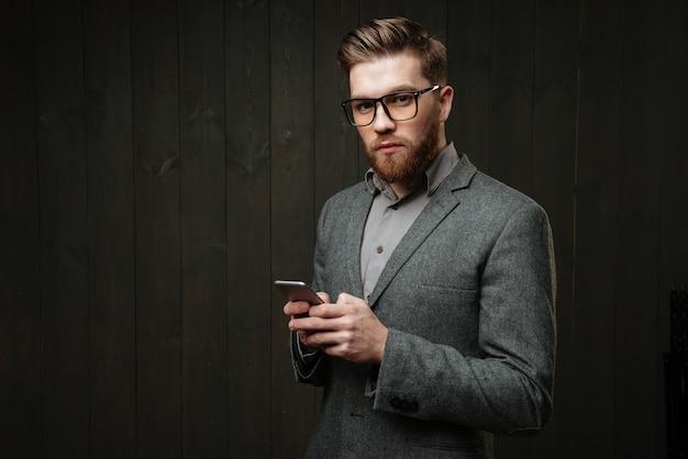 Retrato de um homem sério e inteligente em um terno casual e óculos segurando um telefone celular