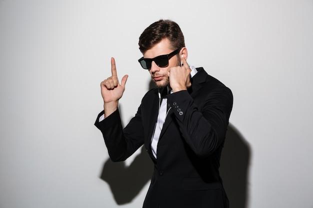 Retrato de um homem sério em fones de ouvido e óculos de sol