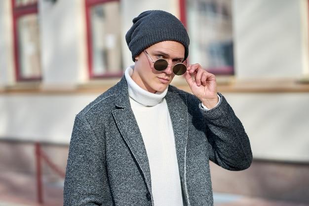 Retrato de um homem sério jovem atraente hipster em óculos de sol, vestindo um casaco cinza, blusa branca e calça jeans preta.