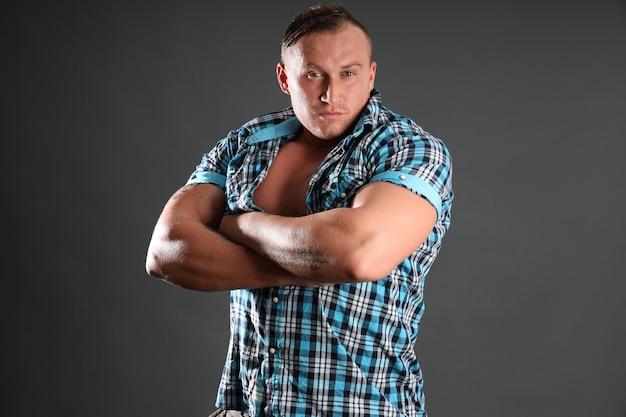 Retrato de um homem sexy desportivo com tatuagem. figura perfeita, bíceps e ombros largos