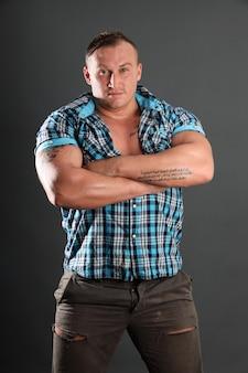 Retrato de um homem sexy e desportivo com tatuagem. figura perfeita, bíceps e ombros largos