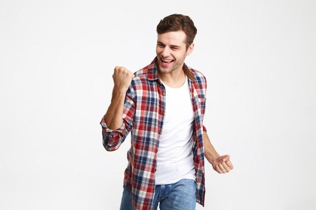 Retrato de um homem sorridente animado comemorando sucesso