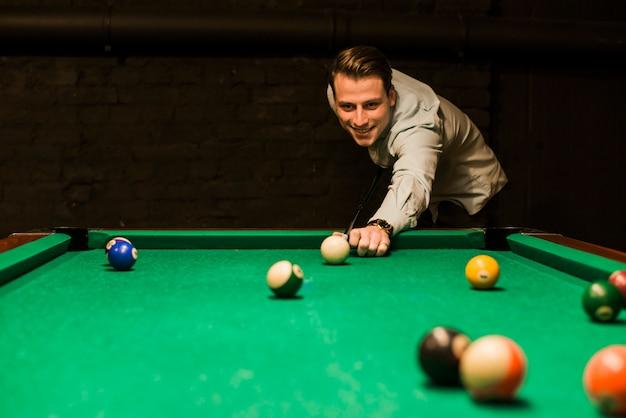 Retrato, de, um, homem sorridente, apontar, a, bola branca, enquanto, jogando snooker