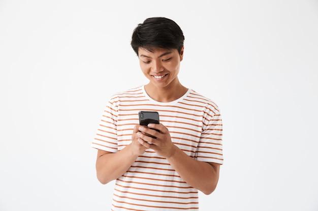 Retrato de um homem sorridente asiático segurando um telefone celular
