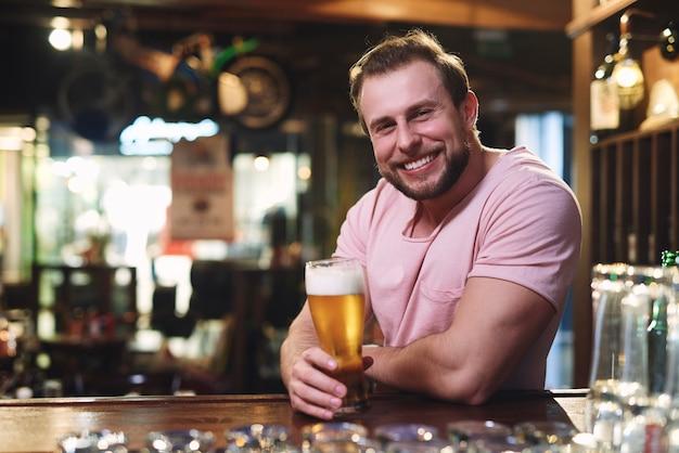 Retrato de um homem sorridente bebendo cerveja no bar