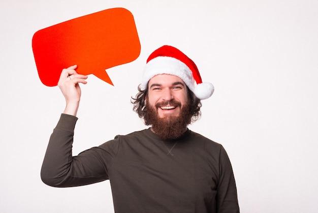 Retrato de um homem sorridente com barba, olhando para a câmera e segurando um balão de fala
