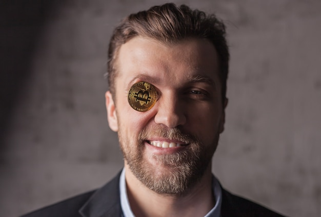 Retrato de um homem sorridente com bitcoin em vez de olhos