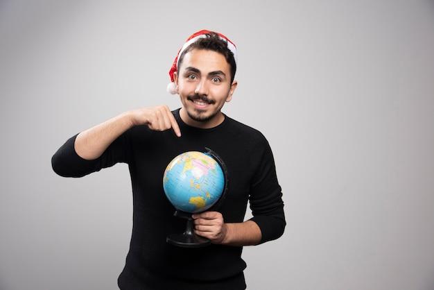 Retrato de um homem sorridente com chapéu de papai noel, apontando para um globo.