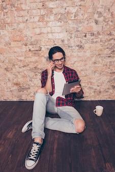 Retrato de um homem sorridente com tablet falando no celular