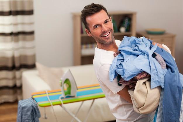 Retrato de um homem sorridente com uma pilha de camisas para passar