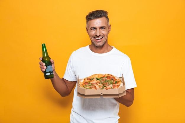 Retrato de um homem sorridente de 30 anos em uma camiseta branca bebendo cerveja e comendo pizza em pé isolado no amarelo
