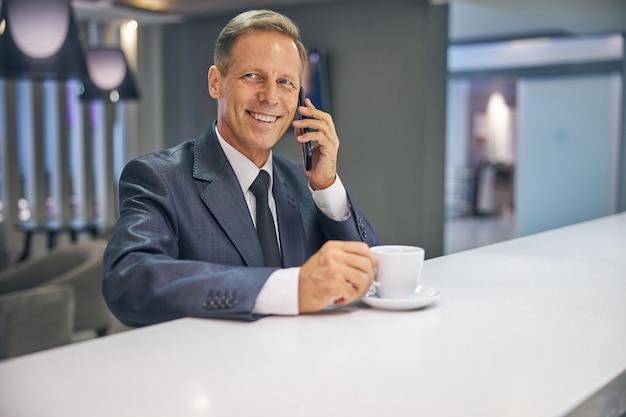 Retrato de um homem sorridente de terno elegante e gravata tomando café e falando no celular no bar