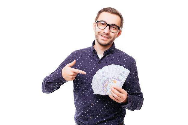 Retrato de um homem sorridente e bem-sucedido de terno e óculos apontando o dedo para um monte de notas de dinheiro isoladas sobre uma parede branca