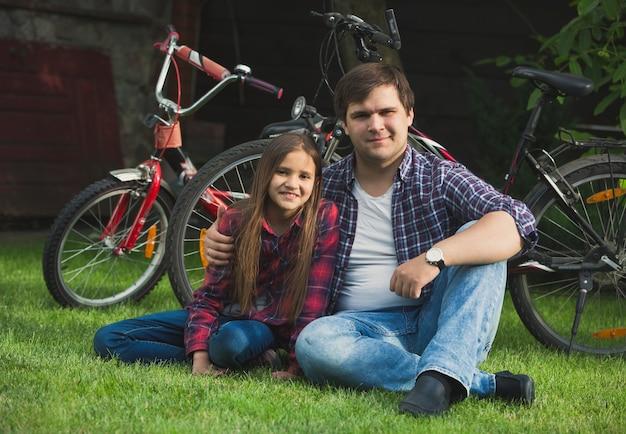 Retrato de um homem sorridente e uma jovem relaxando na grama depois de andar de bicicleta