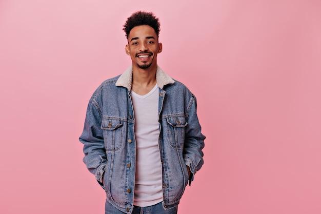 Retrato de um homem sorridente em jaqueta jeans olha para a câmera