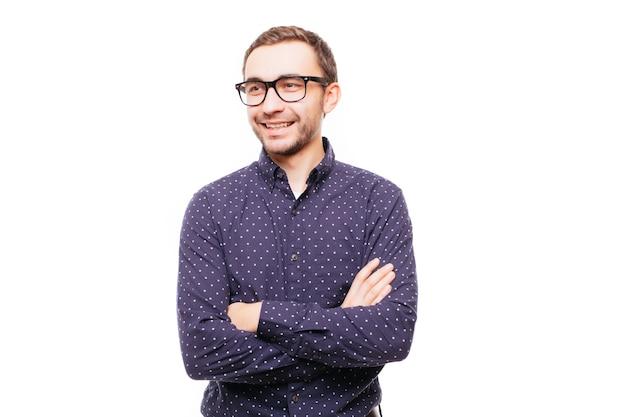 Retrato de um homem sorridente em pé com as mãos cruzadas sobre uma parede cinza