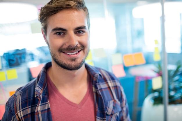 Retrato de um homem sorridente em pé contra notas adesivas na parede de vidro do escritório