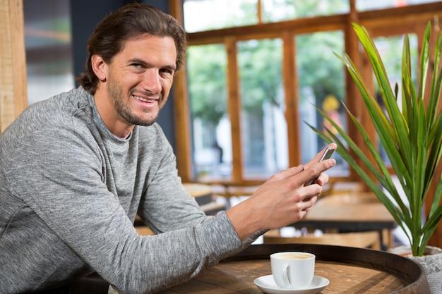 Retrato de um homem sorridente falando no telefone inteligente em uma cafeteria