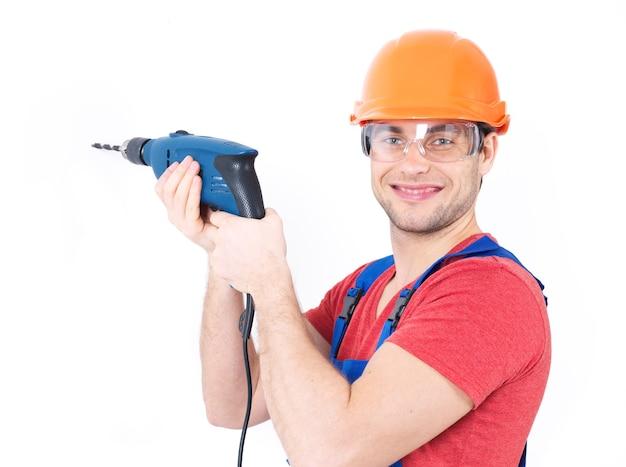 Retrato de um homem sorridente, fazendo um buraco na parede.