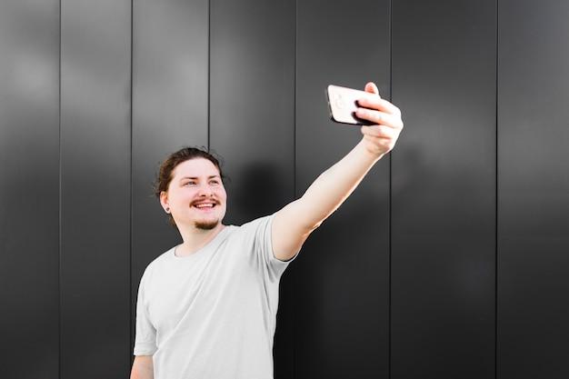 Retrato, de, um, homem sorridente, levando, selfie, ligado, telefone móvel
