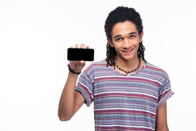 Retrato de um homem sorridente, mostrando a tela do smartphone em branco, isolada em uma parede branca
