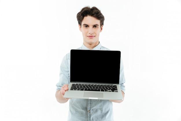 Retrato de um homem sorridente, mostrando o computador portátil de tela em branco